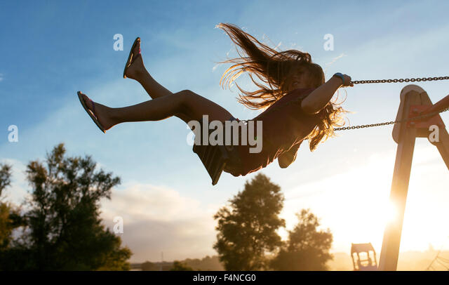 Girl with blowing hair on a swing at backlight - Stock Image