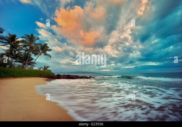 Sunrise ocean waves and palm trees on beach. Maui, Hawaii - Stock Image