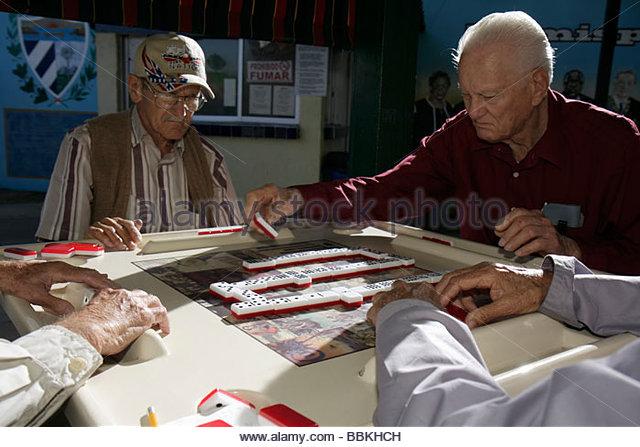 Miami Florida Little Havana Calle Ocho Maximo Gomez Domino Park Hispanic man senior foursome group dominoes tile - Stock Image