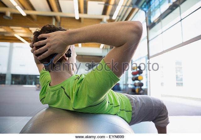 Man doing fitness ball sit-ups at gym - Stock Image