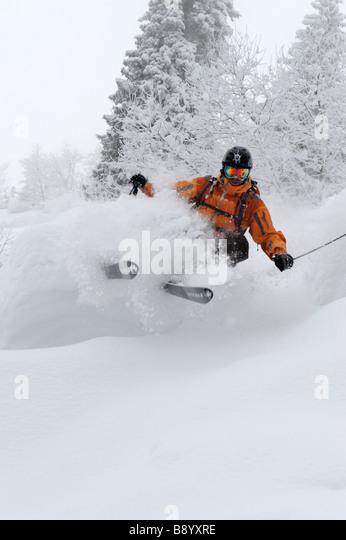 Freerider skies in deep powder during snow fall - Stock Image