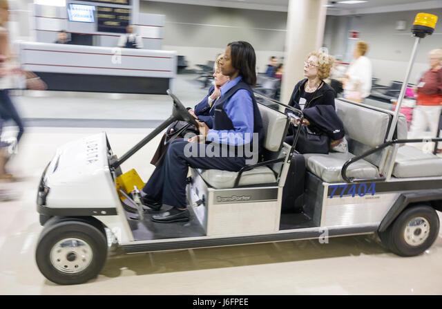 Atlanta Georgia Hartsfield International Airport concourse Black woman women senior assistance courtesy cart transport - Stock Image