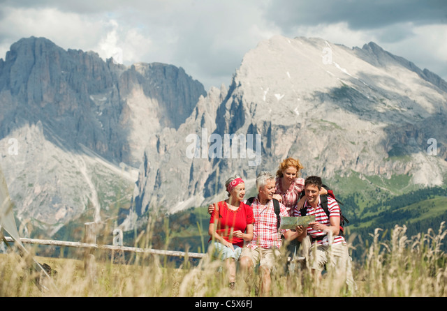 Italy, Seiseralm, Four persons looking at map, portrait - Stock Image