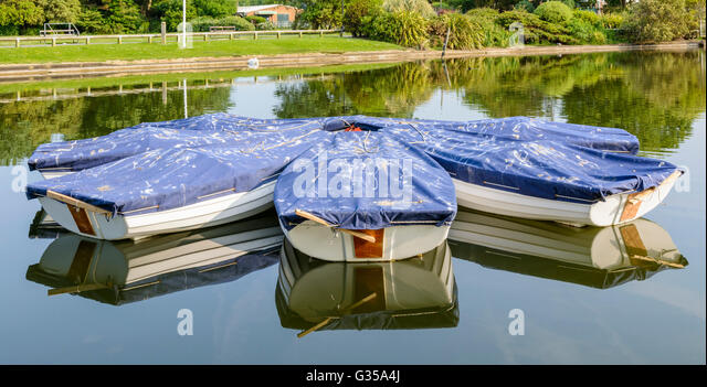 Covered rowing boats on a small boating lake at Mewsbrook Park, Littlehampton, West Sussex, England, UK. - Stock Image