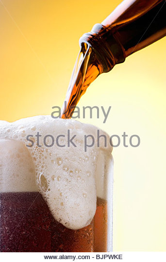 Pouring Beer From Bottle into Overflowing Glass - Stock Image