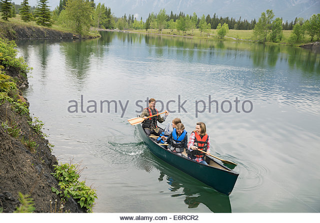 Family rowing canoe in still lake - Stock Image