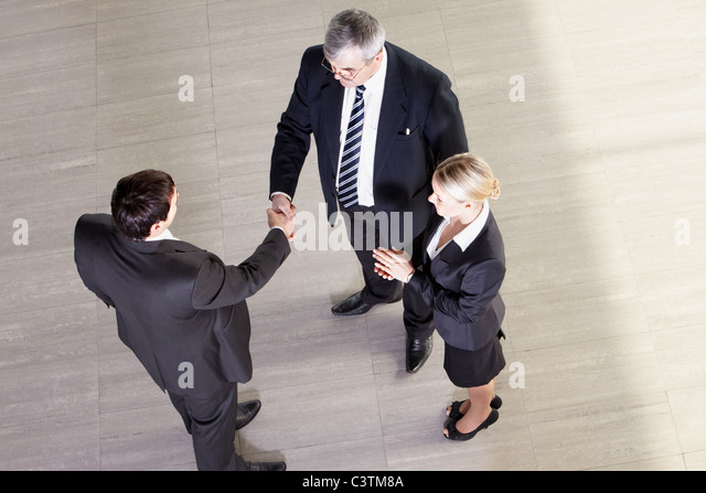 Senior manager shaking hands with his partner, their colleague clapping - Stock Image