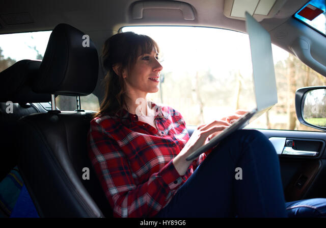 A woman on her laptop in the car - Stock Image