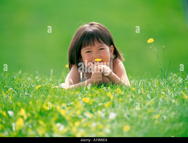 Girl lying down in the meadow holding a yellow flower - Stock-Bilder