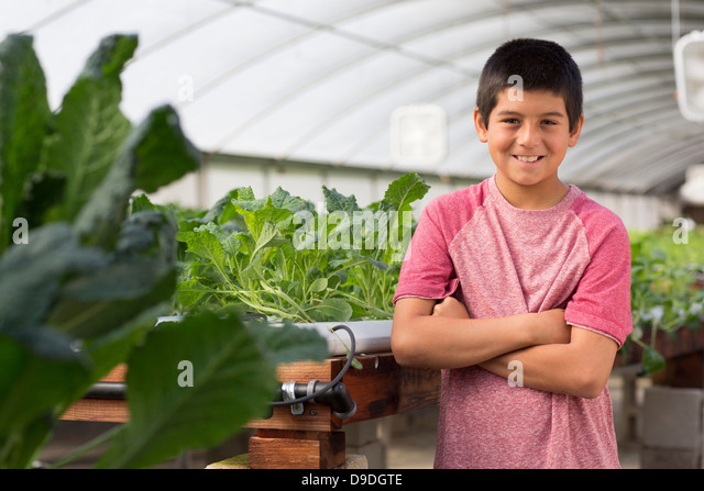 Boy in nursery with arms folded, smiling - Stock Image