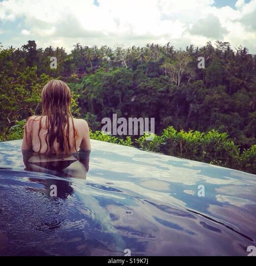 Girl at edge of Infinity pool looking out over Ubud forest - Stock-Bilder