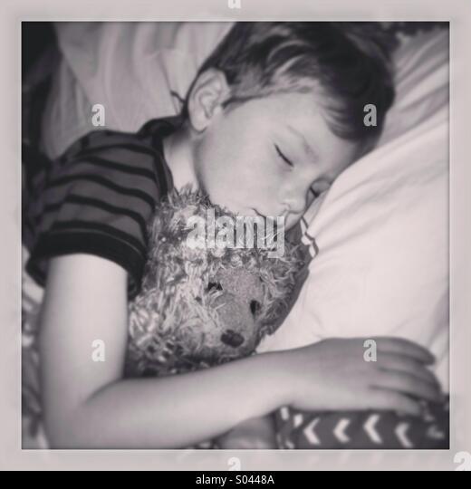 Sleeping boy with teddy bear. - Stock Image