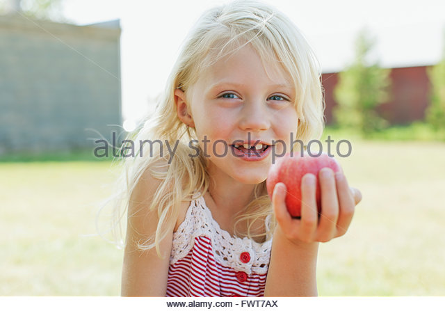 Portrait of cute blonde girl ready to eat an apple. - Stock Image