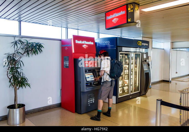 New York New York City NYC Queens LaGuardia Airport LGA terminal ATM automatic teller machine Bank of America man - Stock Image