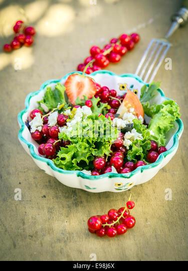 Appetizing Fresh Summer Salad in Bowl on Wooden Background. Good for Vegetarians. - Stock Image