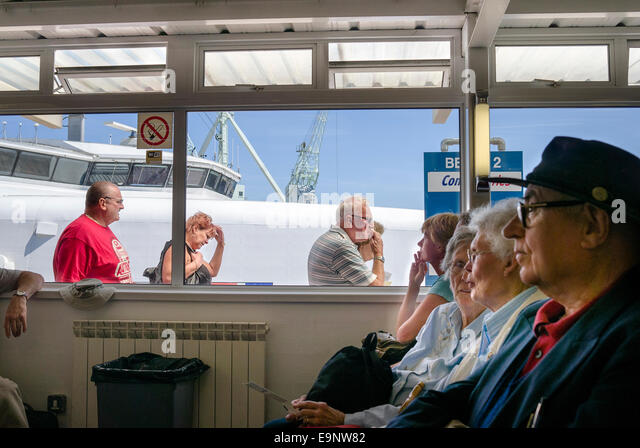 Passengers in the departure lounge at St Peter Port Guernsey watch new arrivals from the cross-channel ferry to - Stock-Bilder