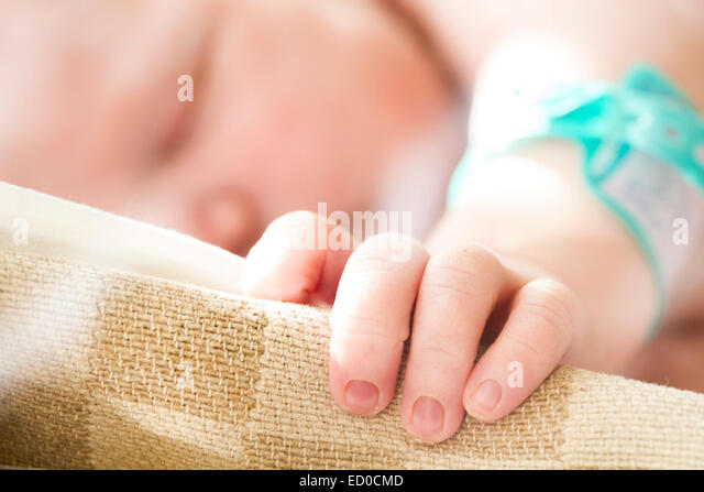 Sleeping baby girl's (0-1 months) hand on cradle - Stock Image