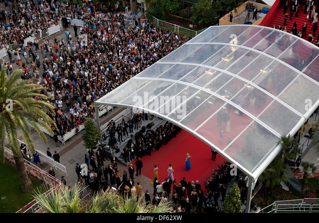 A huge crowd watches celebrities walk down the red carpet at Cannes Film Festival - Stock Image
