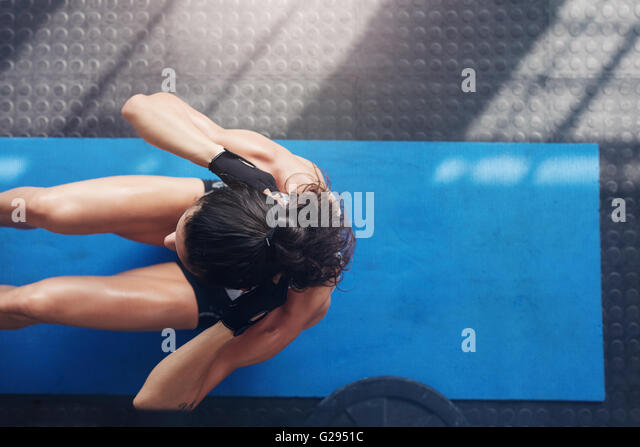 Overhead view of female working out at the gym. Muscular young woman doing sit ups on an exercise mat. - Stock-Bilder