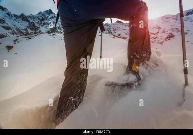 Climber wearing snow shoes walking through deep snow, Monte Rosa, Piedmont, Italy - Stock Image