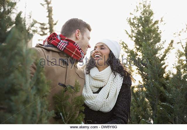 Couple shopping for Christmas tree - Stock Image