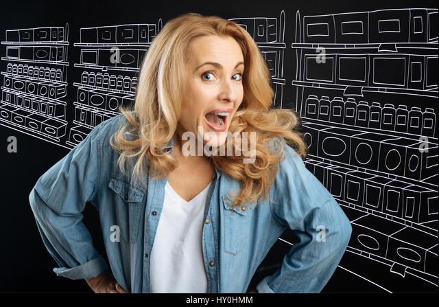 Nice emotional woman visiting a supermarket - Stock Image