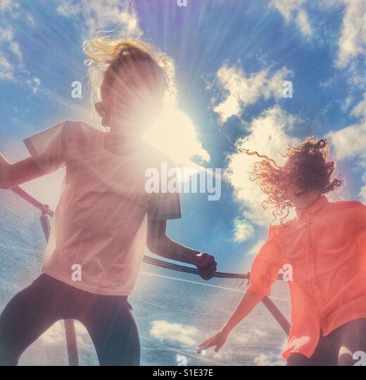 Two girls having fun bouncing on a trampoline - Stock-Bilder