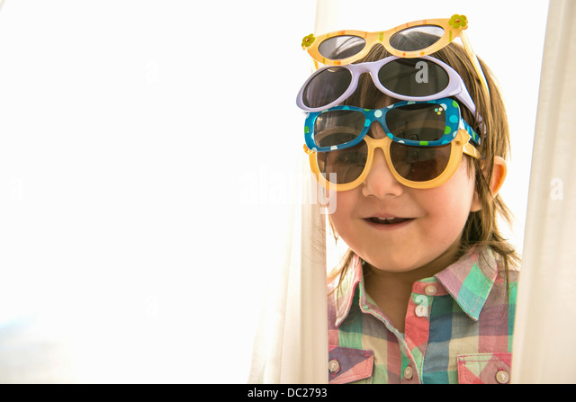 Girl wearing four pairs of sunglasses - Stock Image