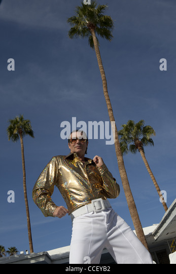 Low angle view of middle-aged man impersonating Elvis Presley - Stock Image