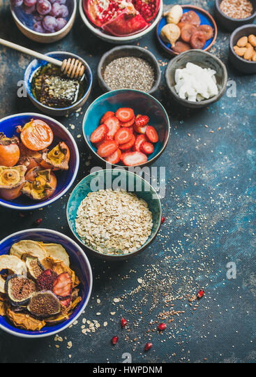 Ingredients for healthy vegetarian breakfast over dark blue plywood background - Stock Image