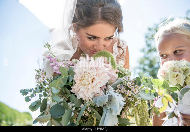 A bride and her young bridesmaid with their bouquets - Stock Image