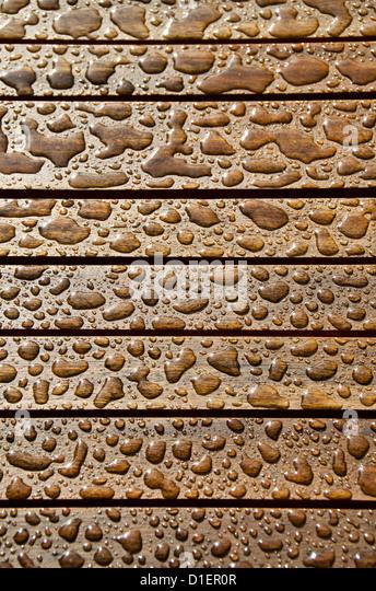 Rain drops on teakwood - Stock-Bilder
