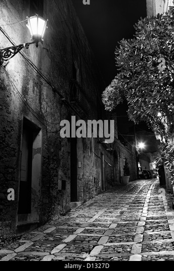 Narrow cobblestone street illuminated by light at night - Stock Image