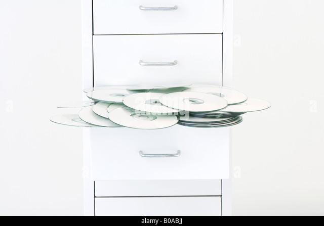 CDs spilling out of filing cabinet drawer - Stock Image