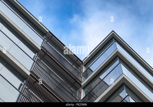 Abstract fragment of modern architecture, walls made of glass and concrete over blue cloudy sky background - Stock Image