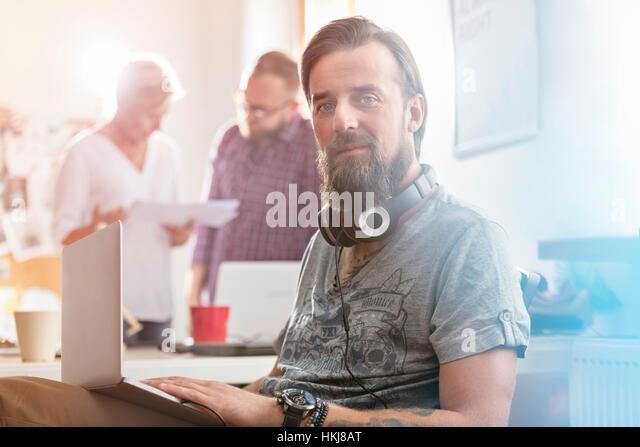 Portrait smiling male design professional with headphones using laptop in office - Stock-Bilder