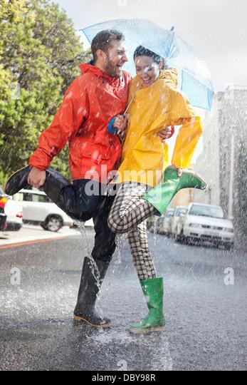 Happy couple in wellingtons splashing in rainy street - Stock-Bilder