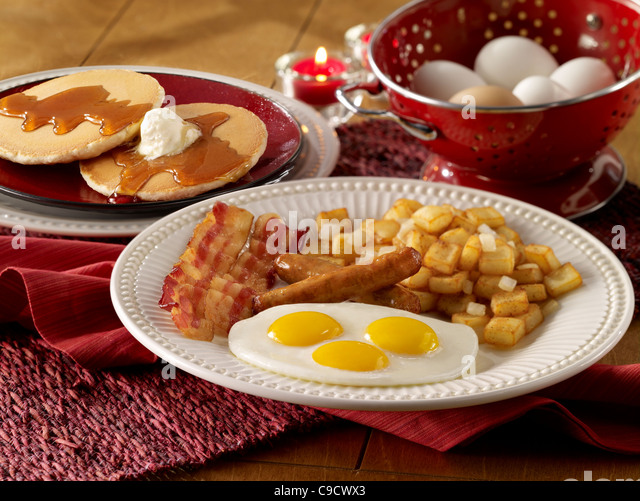 Eggs, sausage, bacon and potato breakfast with a stack of pancakes - Stock Image