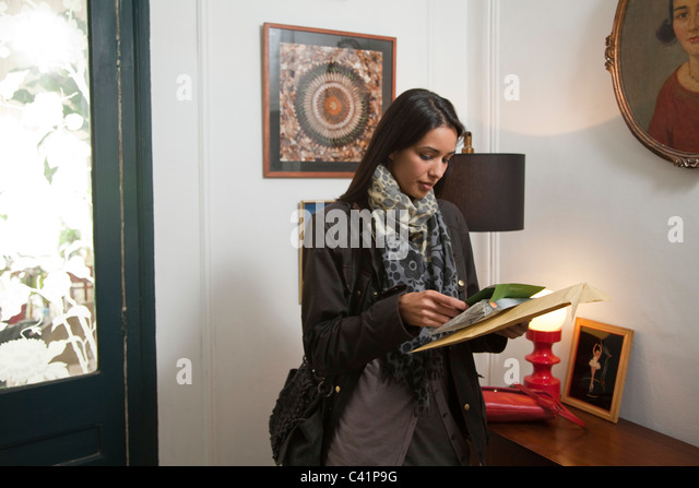 Woman opening her mail - Stock Image