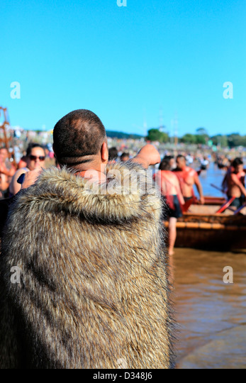 Maori man in traditional feathered cloak on Te Tii beach during Waitangi Day celebrations - Stock-Bilder
