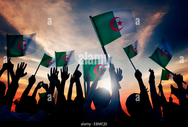 Silhouettes of People Holding Flag of Algeria - Stock Image