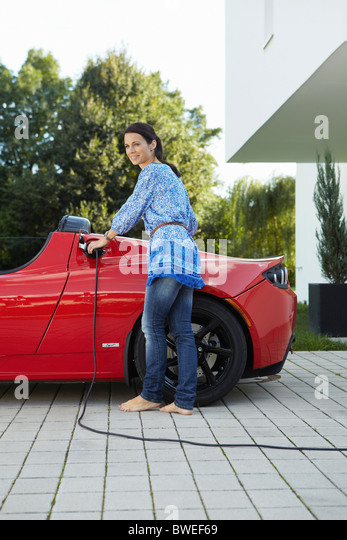 Women filling up her electric car - Stock Image
