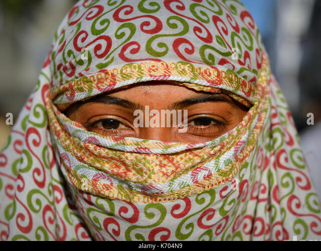 Young Indian woman with beautiful eyes, covering her hair and face with a trendy secular, red-and-green headscarf; - Stock Image