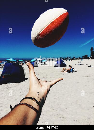 Cropped Image Of Hand Throwing Rugby Ball At Coronado Beach - Stock Image