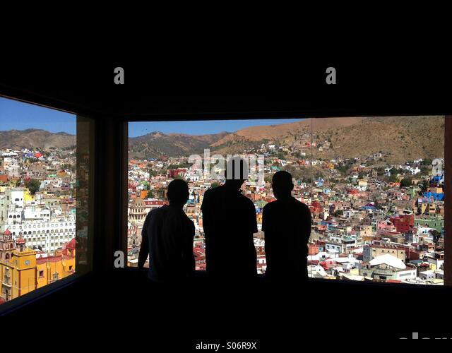 Three people looking over Guanajuato Mexico from a funicular window - Stock Image