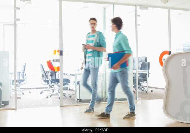 Full-length of businessmen walking at creative work space - Stock Image