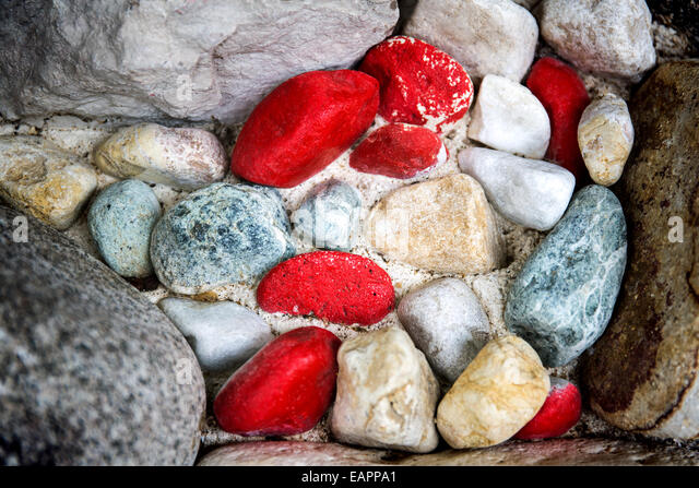A close up shot from above of multicolored pebbles and rocks. The colors of the pebbles vary from blue grey to orange - Stock-Bilder