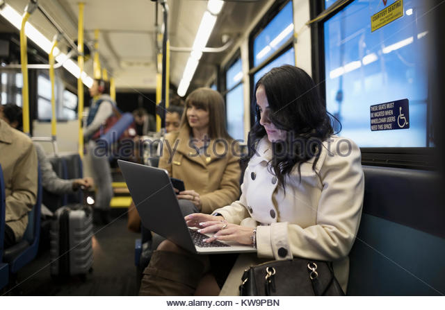 Businesswoman commuter working at laptop on bus - Stock Image