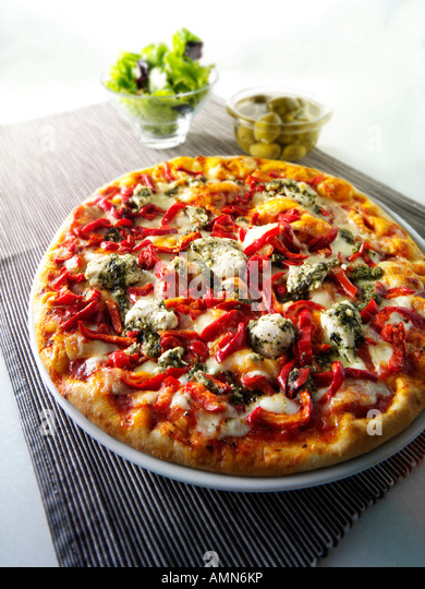 Whole chicken and pepper topped pizza - Stock Image