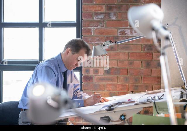 Architect making plans at drawing board - Stock-Bilder